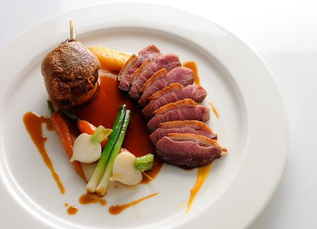 Pan-roast duck with sweet potato fondant, baby vegetables and cherry brandy sauce