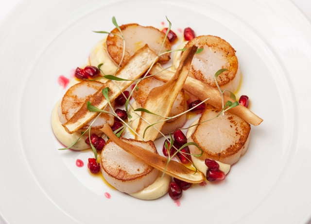 Scallops with curried parsnip purée, parsnip crisps and pomegranate