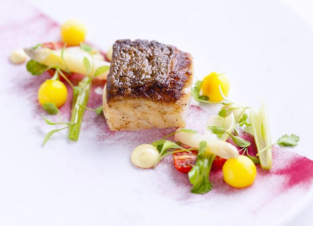 Roast fillet of cod with saffron potatoes and tomatoes