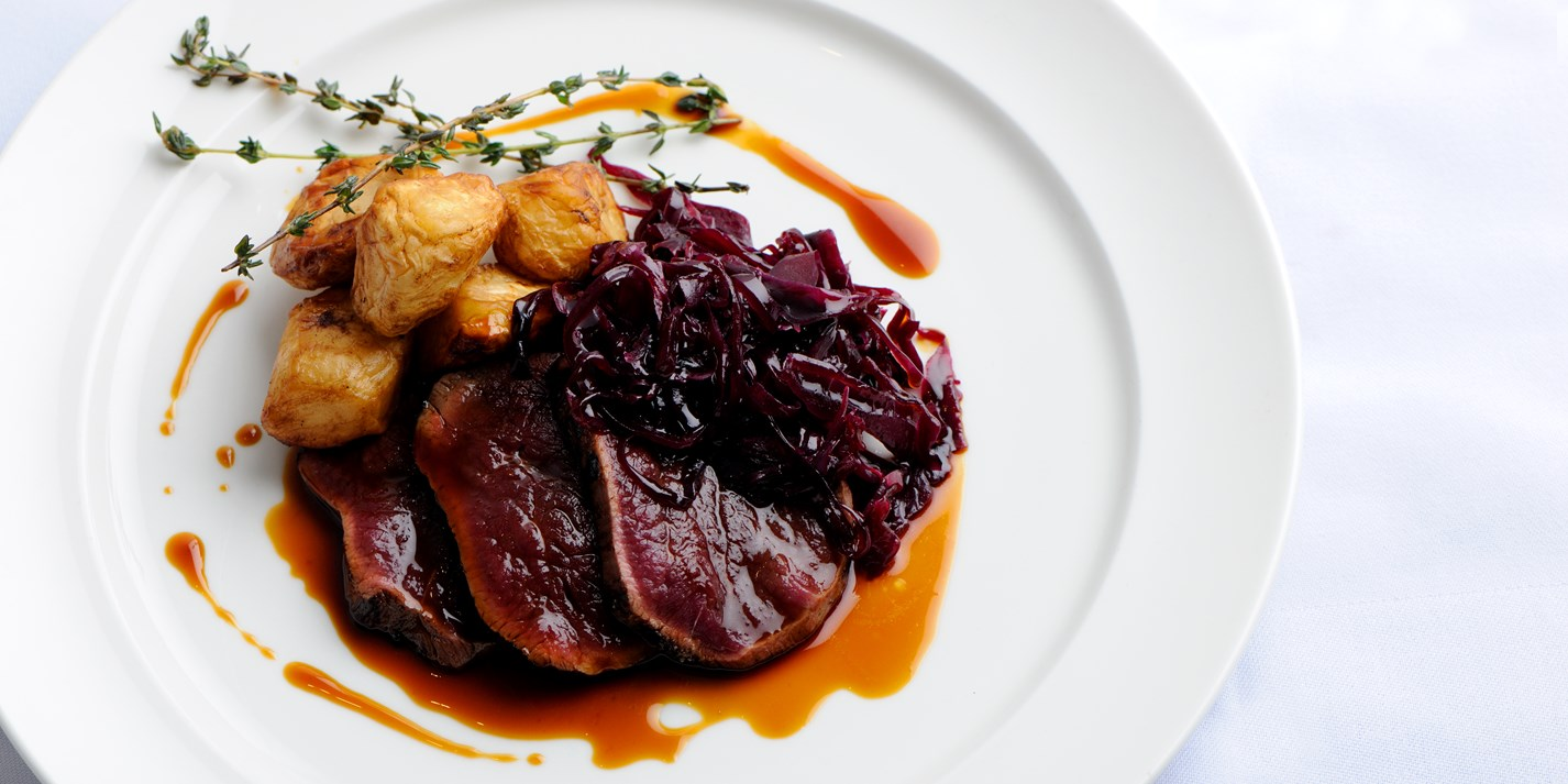 Venison leg cooked in hay with roast celeriac and braised red cabbage